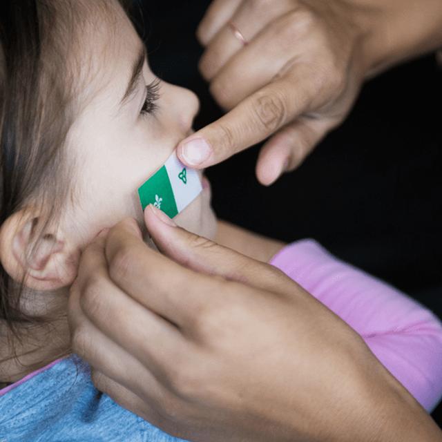Petite fille avec un tatouage de drapeau franco-ontarien sur la joue
