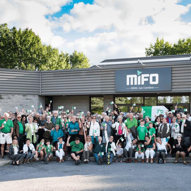 Groupe de personnes avec des drapeaux franco-ontariens devant le MIFO