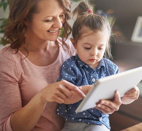 Mère et jeune fille qui complète une demande en ligne sur tablette mobile