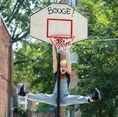 Jeune femme qui se laisse pendre par les bras sur un panier de basketball