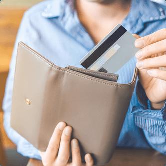 Femme qui sort une carte de crédit de son portefeuille