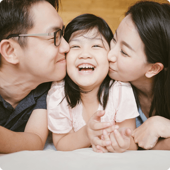 Enfant avec parents qui donnent des baisers sur les joues