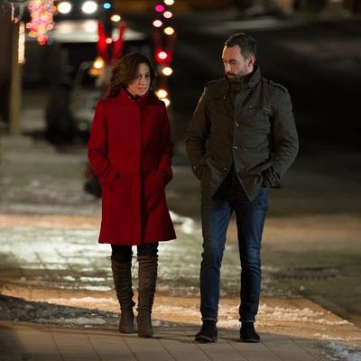 Homme et femme qui marchent sur un trottoir enneigé