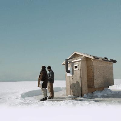 Deux personnes dehors devant une cabane à pêche l'hiver