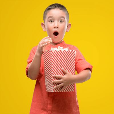 Enfant qui mange du maïs soufflé devant un arrière-plan jaune