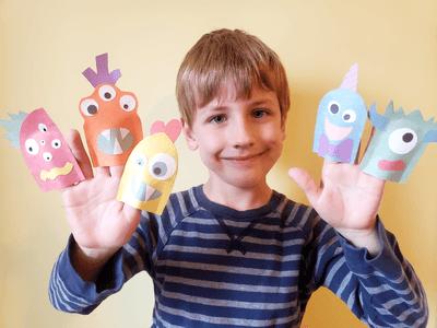 Jeune garçon avec marionnettes de monstres sur les doigts