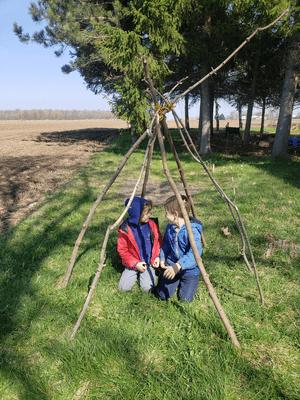 Deux jeunes garçons sous une tente de branches